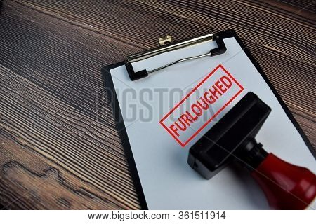 Red Handle Rubber Stamper And Furloughed Text Isolated On The Table.