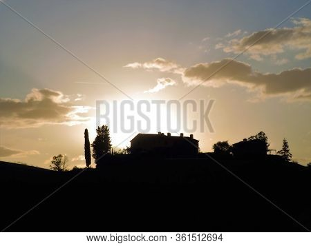 Silhouette Of A Country-house And Cypress On A Hill In Tuscany Region Of Italy, Landscape With Sunri