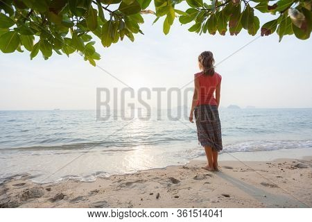 Young woman in hippie pants enjoys solitude on the sandy tropical beach