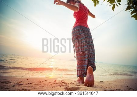 Young woman in hippie pants dances barefoot on the sandy tropical beach at sunset. Focus on the foot