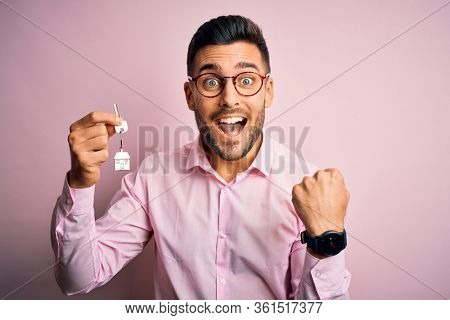 Young real estate business man holding new house keys over pink background screaming proud and celebrating victory and success very excited, cheering emotion