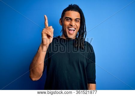 Young handsome african american afro man with dreadlocks wearing casual t-shirt pointing finger up with successful idea. Exited and happy. Number one.