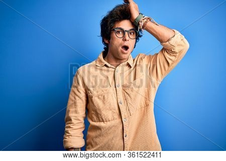 Young handsome man wearing casual shirt standing over isolated blue background surprised with hand on head for mistake, remember error. Forgot, bad memory concept.