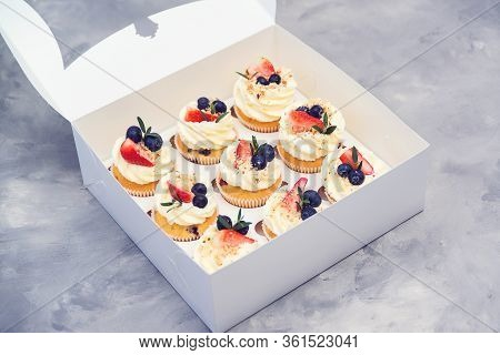 Set Of Different Delicious Cupcakes. Paper Box With Fruit Cupcakes. Holiday Cupcakes With Strawberry