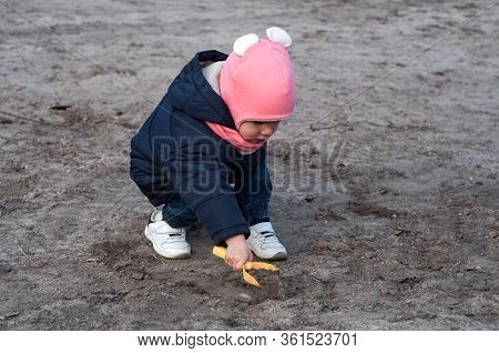 Little Toddler Girl Alone Playing In The Soil With Shovel