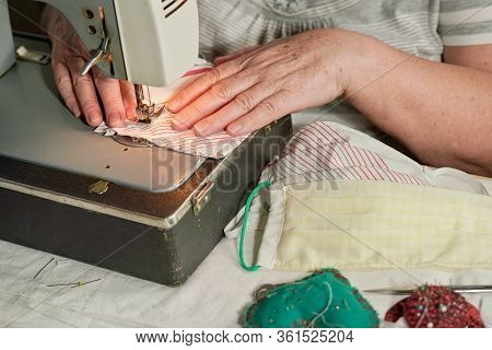 Elderly Senior Woman Working On Old Sewing Machine - Making Home Made Face Masks Against Coronavirus
