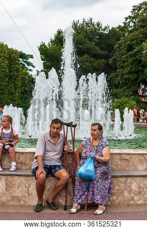 Anapa, Russia - July 26, 2017: Aged Disabled People Sit Together Outdoors By Fountain On Sea Embankm