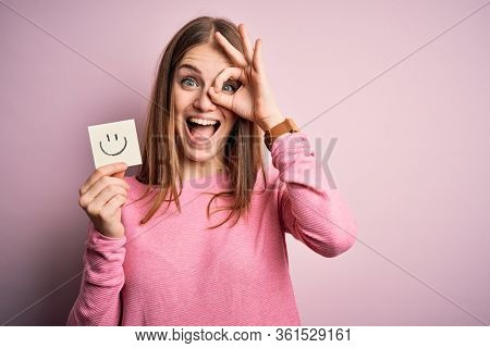 Young beautiful redhead woman holding reminder paper with smile emoji message with happy face smiling doing ok sign with hand on eye looking through fingers