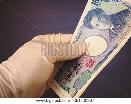 A Hand In A Flesh-colored Rubber Glove Holds Out A Bundle Of Japanese Money. Above Is A 1000 Yen Bil