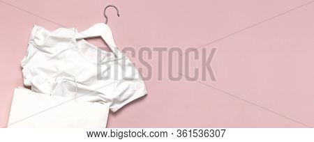 White Shirt, White Wooden Hangers, Paper Bag On Pink Background Top View Flat Lay. Fashion Discounts