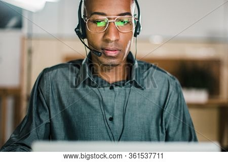 Concentrated Call Center Operator Talking With Client. Front View Of Thoughtful Call Center Operator