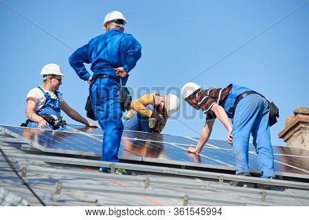 Male Team Engineers Installing Solar Photovoltaic Panel System. Electricians Mounting Blue Solar Mod