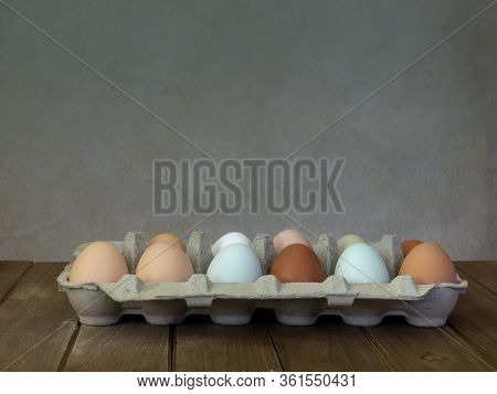 One Dozen Unwashed Colorful Chicken Eggs In Open Cartonon On Wooden Surface Viewed From The Side And