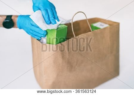 Disinfection of food home delivery sanitizing packages of online shopping bag with disinfecting wipes. Sanitizing surfaces of packages on groceries with gloves. COVID-19 precaution hygiene.