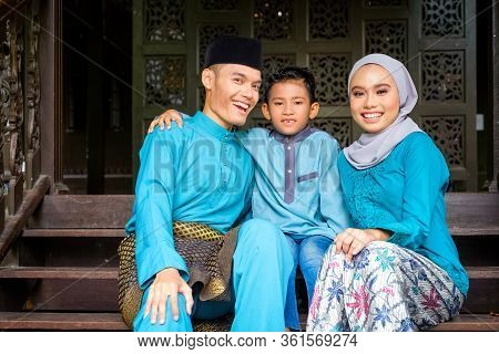 A Portrait Of Young Couple Of Malay Muslim In Traditional Costume With His Son During Eid Al-fitr Ce