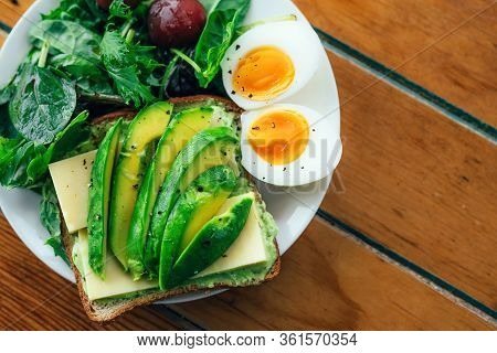 Toast With Avocado, Boiled Egg, Spinach And Tomatoes On White Plate With Knife And Fork On Serviette