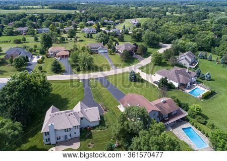 Aerial view of an upscale tree-lined neighborhood in a Chicago suburban city in summer.