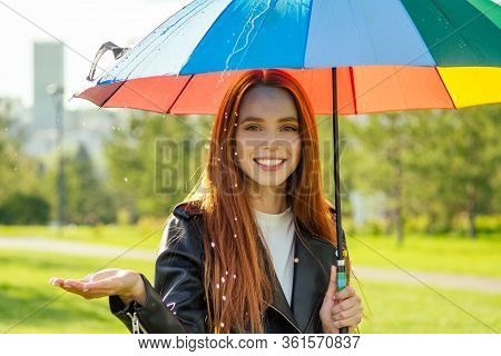 Redhaired Ginger Woman Standing Under Colorful Umbrella In Summer Park Checking For Rain Rainbow