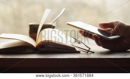 Hand Holds Smartphone, Open Old Book And Cup Of Coffee Near The Window