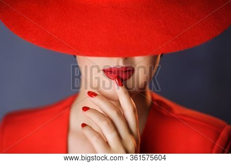 Portrait Of A Woman In Red Clothes, Having Put A Finger To Her Lips. A Woman With Red Lipstick, In A
