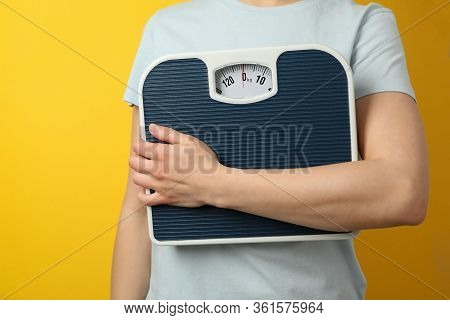 Woman Holds Scales On Yellow Background. Weight Loss