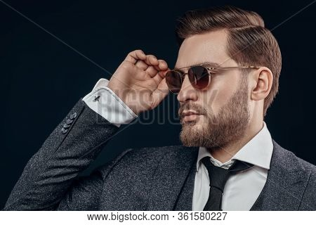 Portrait of a handsome businessman wearing suit and glasses on a black background. Men's beauty, fashion. Optics for men. Copy space.