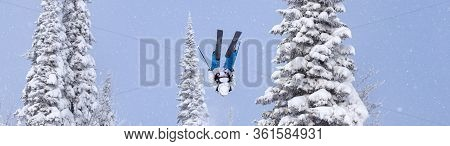 a Freerider in bright gear jumps between Christmas trees with a backflip element. prof skier in a be