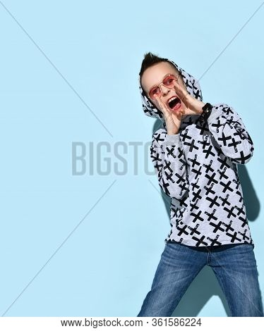 Teenage Male In Sunglasses And Hood, Blue Jeans And Stylish Hoodie, Black Bracelet. Calling Someone