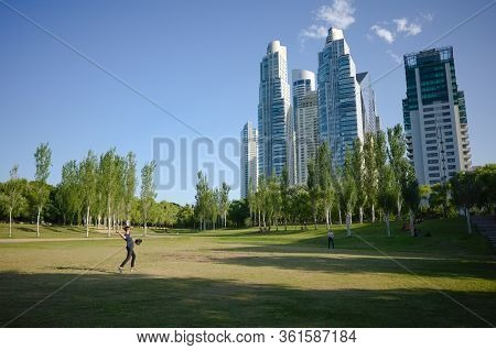 Buenos Aires, Argentina - January, 2020: Young Man Playing Baseball Game In A City Park Near High Of