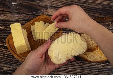 Someone Puts A Slice Of Cheese On Fresh Wheat Toast With Butter And A Wooden Butter Dish With A Piec