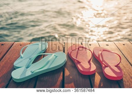Two Pairs Of Flip Flops At The Wooden Pier During Sunset. Luxury Vacation Resort. Holiday Getaway Co