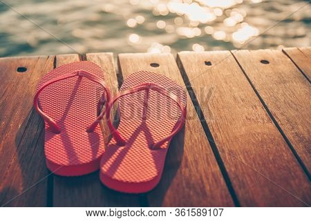 Flip Flops At The Wooden Pier During Sunset. Luxury Vacation Resort. Holiday Getaway Concept. Horizo