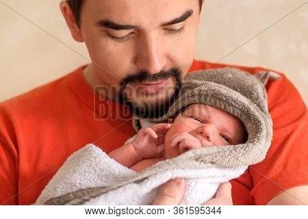Young Father Holding In Arms Little Newborn Baby Daughter After Bathing. Close Up Portrait Of Infant