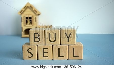 To Buy Or Sell A House Cubes Form The Words Buy And Sell In Front Of A Miniature House.