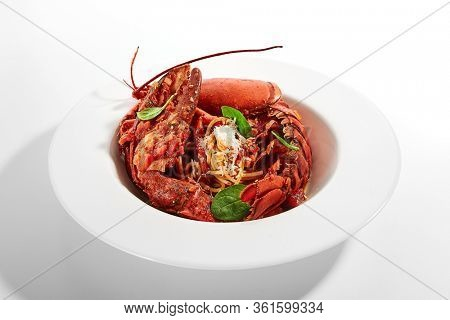 Spaghetti with lobster. Served traditional Italian cuisine. Pasta with grated parmesan cheese and seafood in plate. Italy luxury culinary. Restaurant food portion, delicious supper, main course