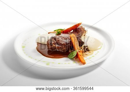 Beef loin on bone close up. Served roasted meat with baked sweet potato and forest mushrooms ragout in plate. Gourmet culinary, gastronomy. Restaurant food portion, cooked main course