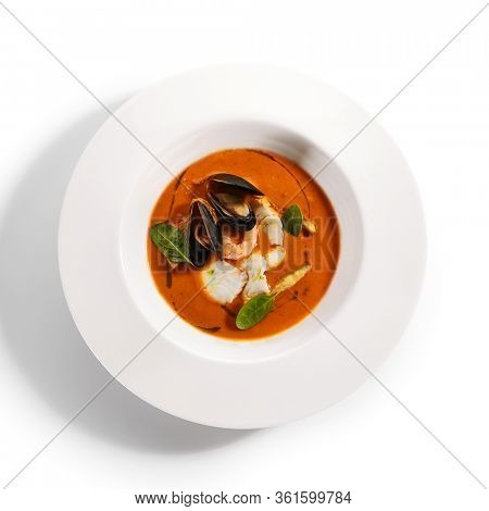 Bouillabaisse in white bowl. Served main course top view. French seafood, soup with fish and mussels. Restaurant food portion, main course. France cuisine. Dinner, gourmet meal in plate