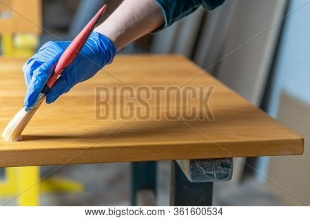 Applying Varnish To The Wooden Surface By Means Of A Brush In The Joinery