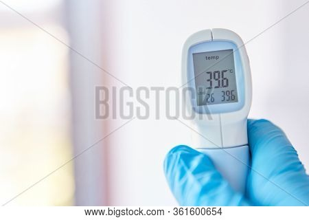 Display of clinical thermometer shows fever in Covid-19 patient with coronavirus epidemic in hospital