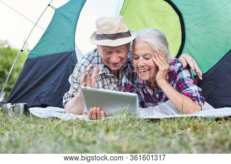 Senior couple having fun at the video chat online with the tablet computer while camping
