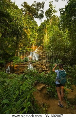 Woman Backpacker Taking Photo Of The Pha Charoen Waterfall Phop Phra District, Tak, Thailand