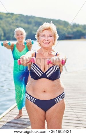 Two vital senior women doing dumbbells in the summer on vacation at the lake
