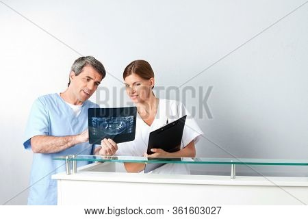 The dentist and dental assistant analyze the x-ray image of a bit