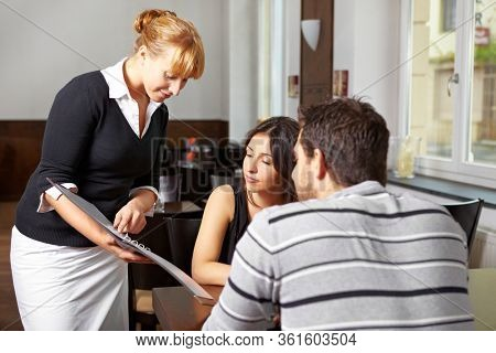 Waitress in the restaurant recommends daily menu in the menu