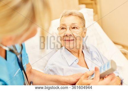 Nursing service cares for a bedridden senior woman in the hospital bed in the nursing home