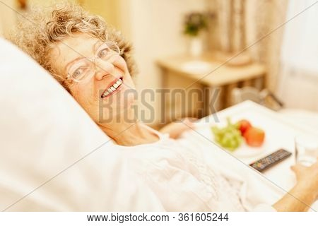 Happy senior woman is lying in bed in her senior citizen home or retirement home