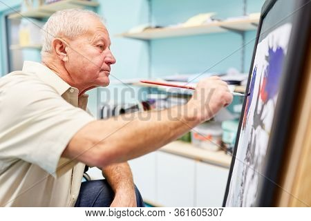 Senior with dementia paints a picture in the creative painting therapy at the retirement home