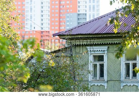 Old House Against The Background Of High-rise Buildings. A Large Wooden House. Old Wooden Architectu