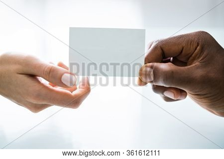 Close-up Of Two Businesspeople Hand Exchanging Visiting Card In Office
