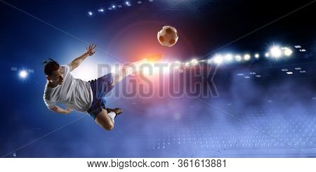 Football player on stadium jumps to kick a ball